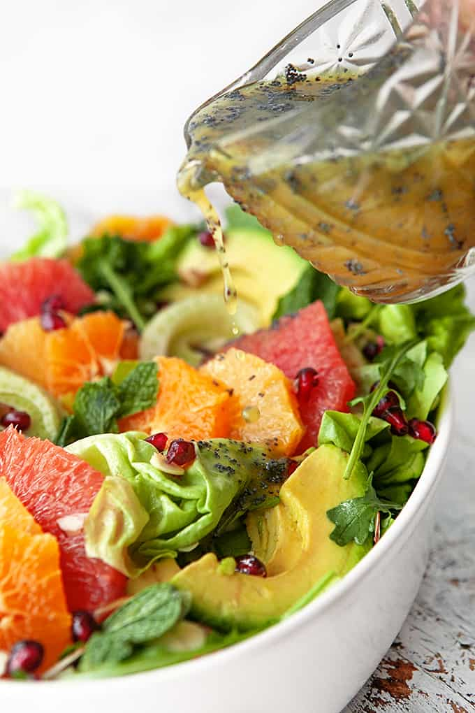Pouring poppy seed dressing on salad