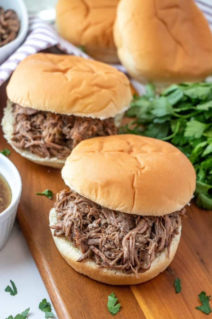 Two Slow Cooker Beef Dip sandwiches on a cutting board