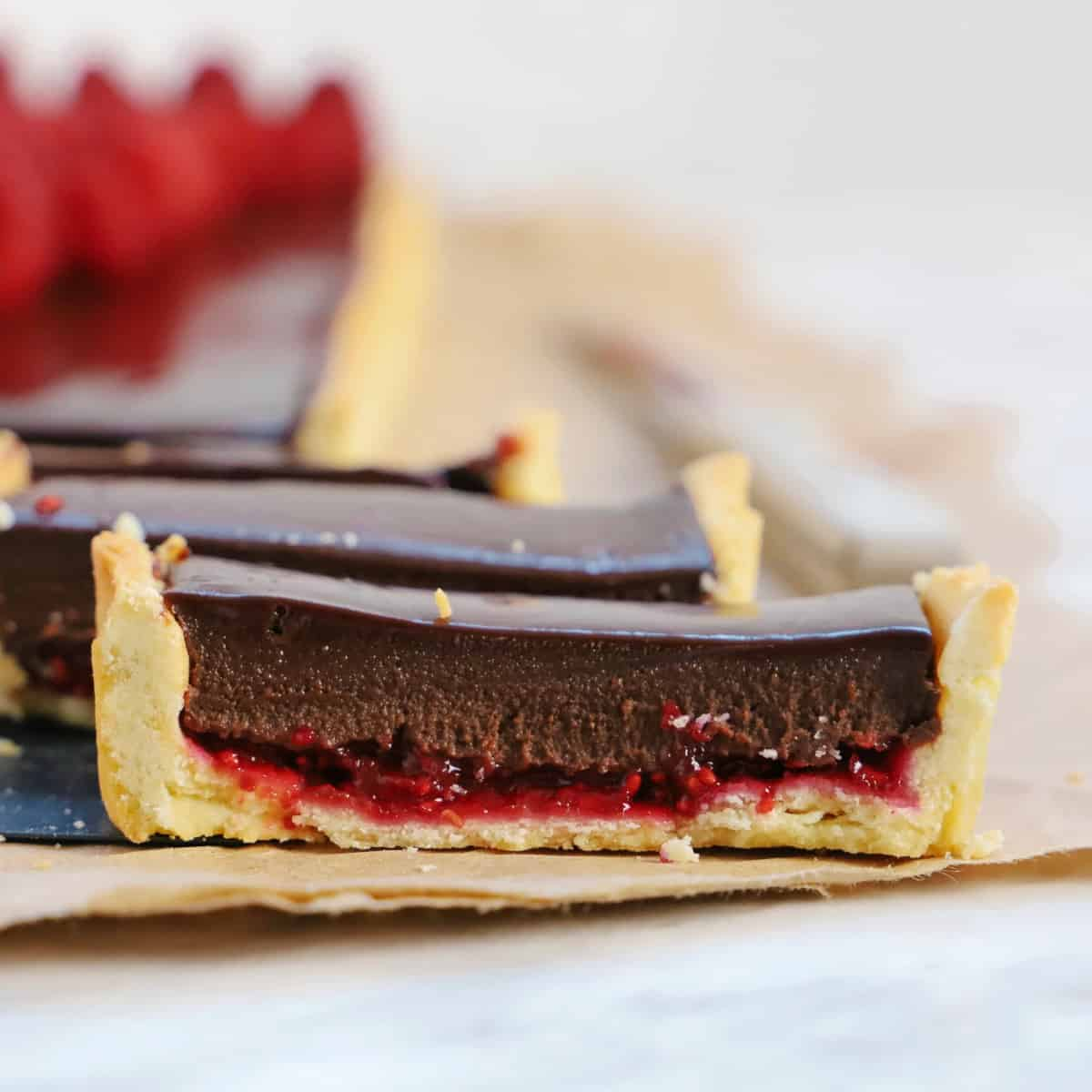 Square photo of a close up of a sliced chocolate tart with raspberry jam.