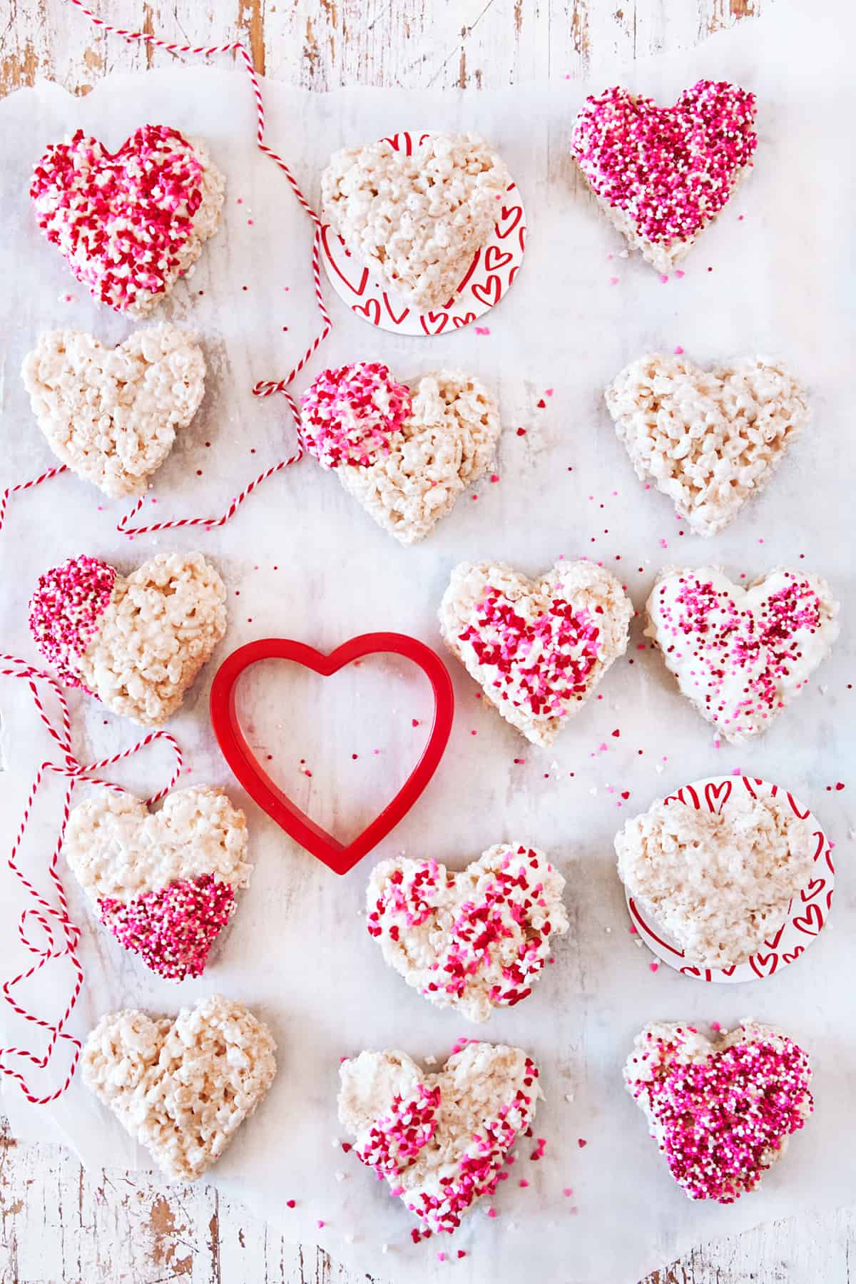 Heart shaped rice Krispie treats with a heart cookie cutter and red and white string.