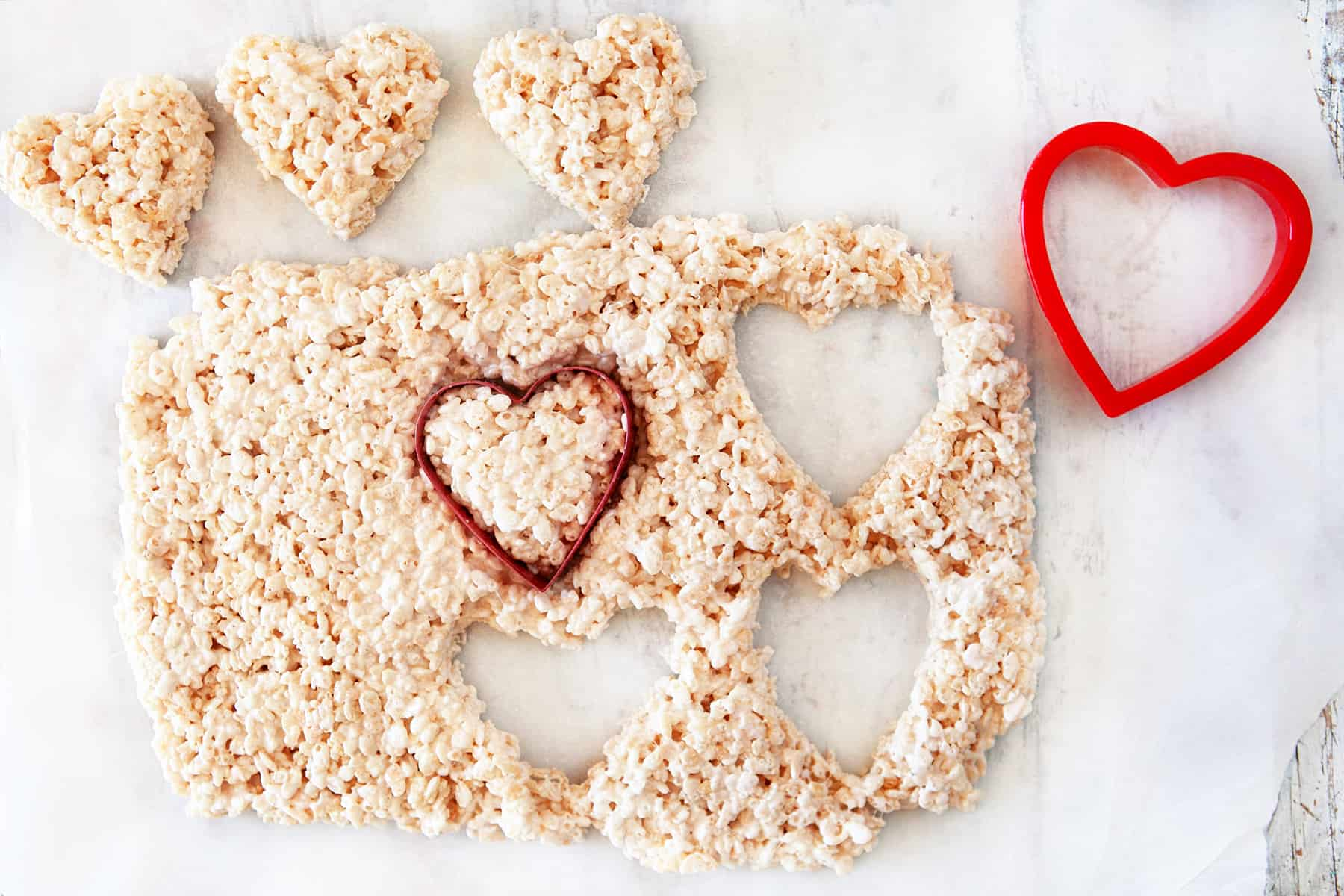 Cutting out heart shapes from rice krispie treats.