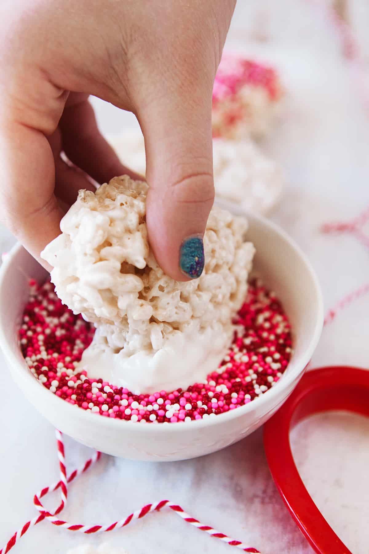 Dipping rice Krispies in sprinkles.