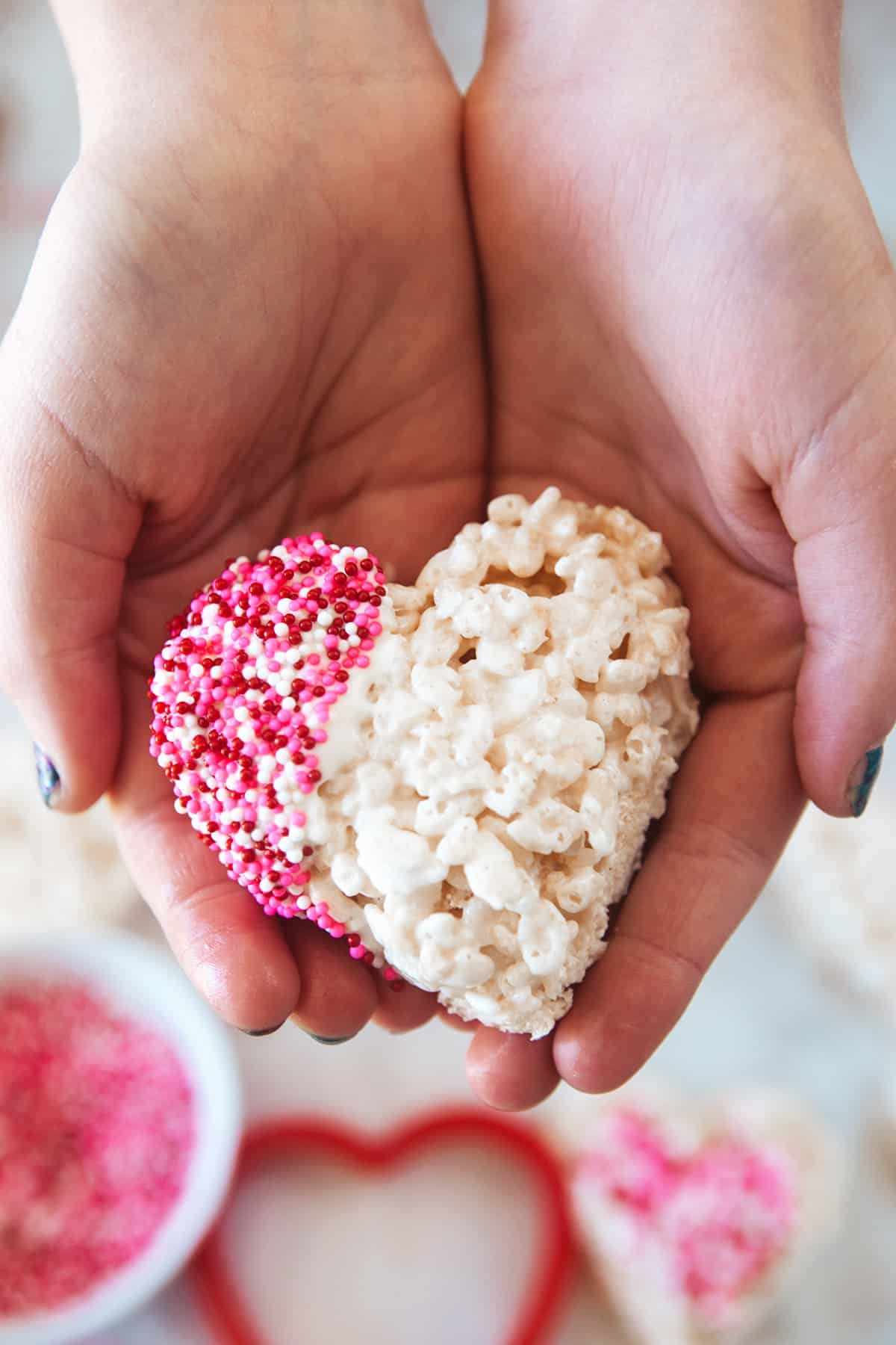 Hands holding a heart rice Krispie treat.