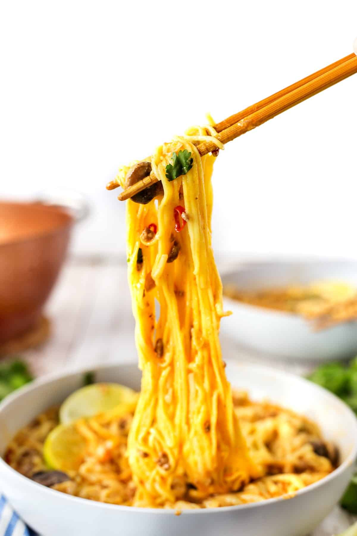 Pulling noodles from the bowl with chopsticks.