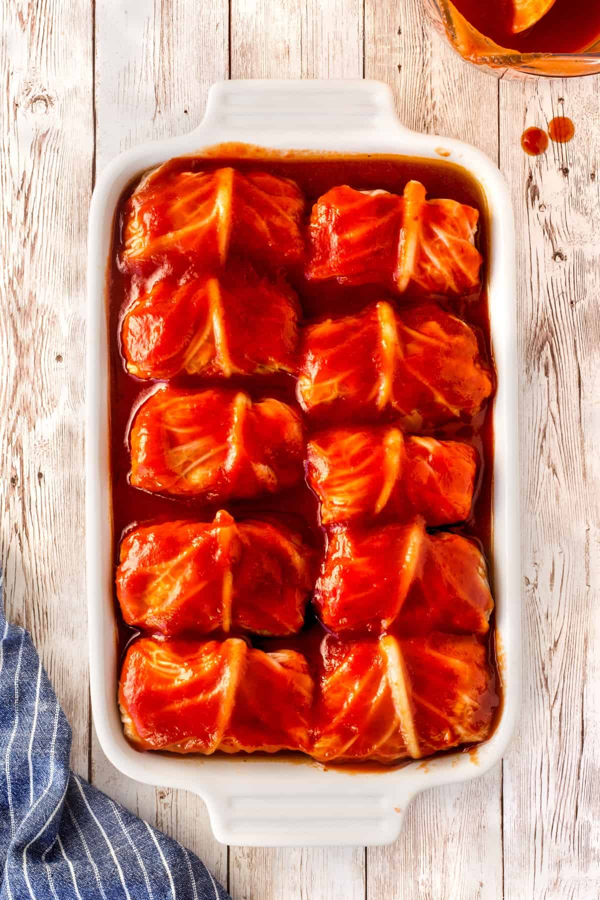 """Overhead of unbaked cabbage rolls in a casserole, 9x13""""."""