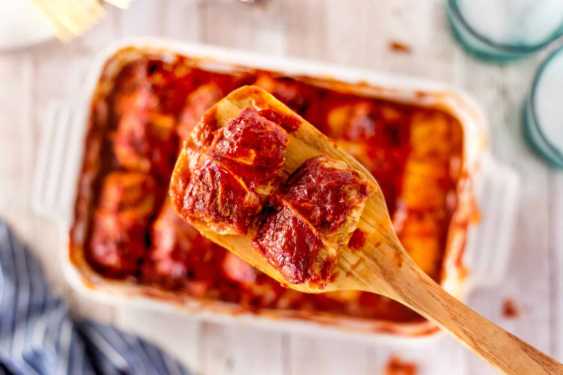 Overhead of two cabbage rolls on a wooden paddle