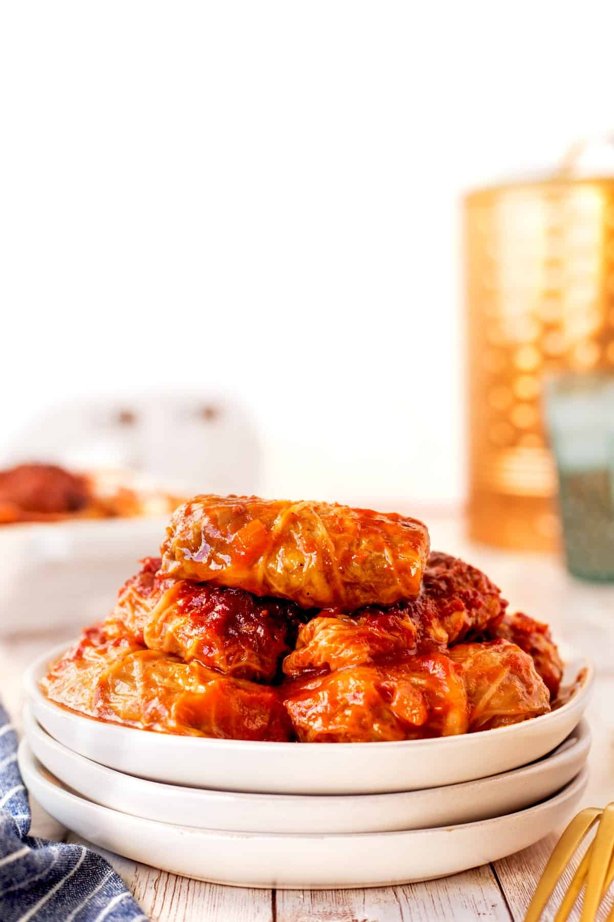 Cabbage rolls stacked on white plates.