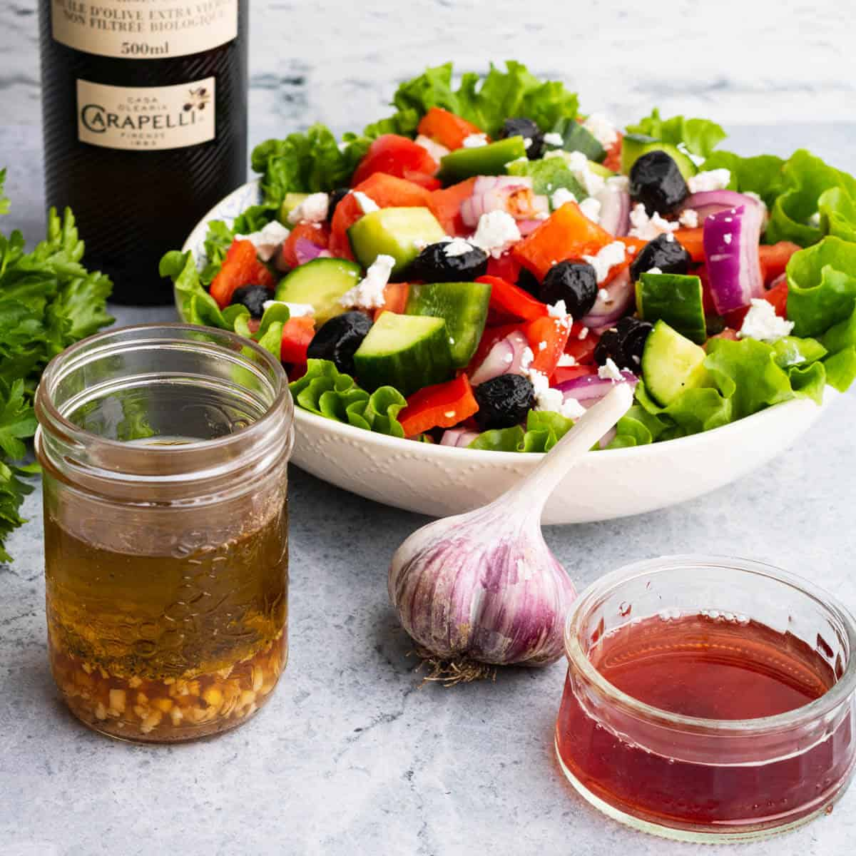 A salad surrounded by red wine dressing ingredients.