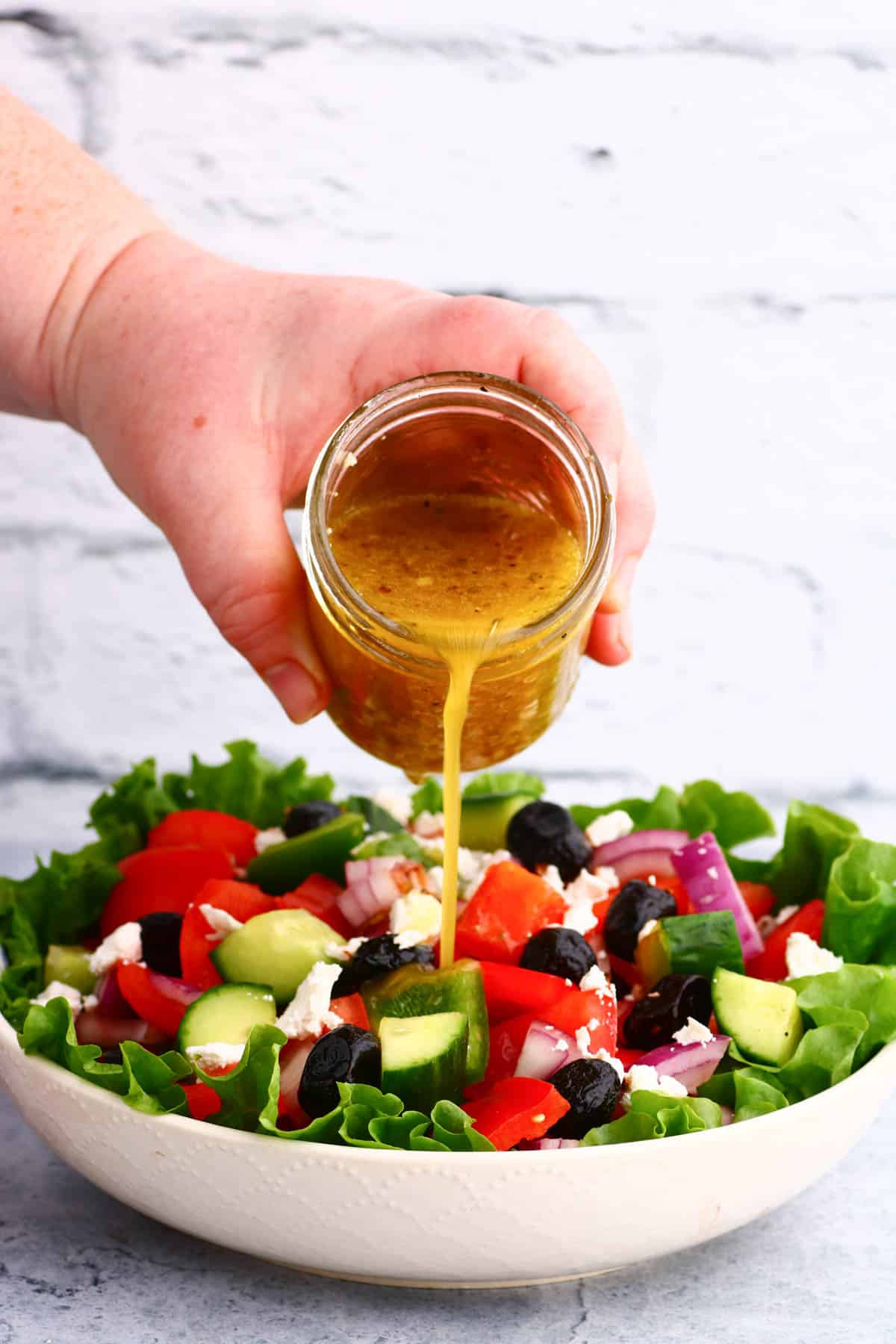 Salad dressing being poured on a bright chopped salad.
