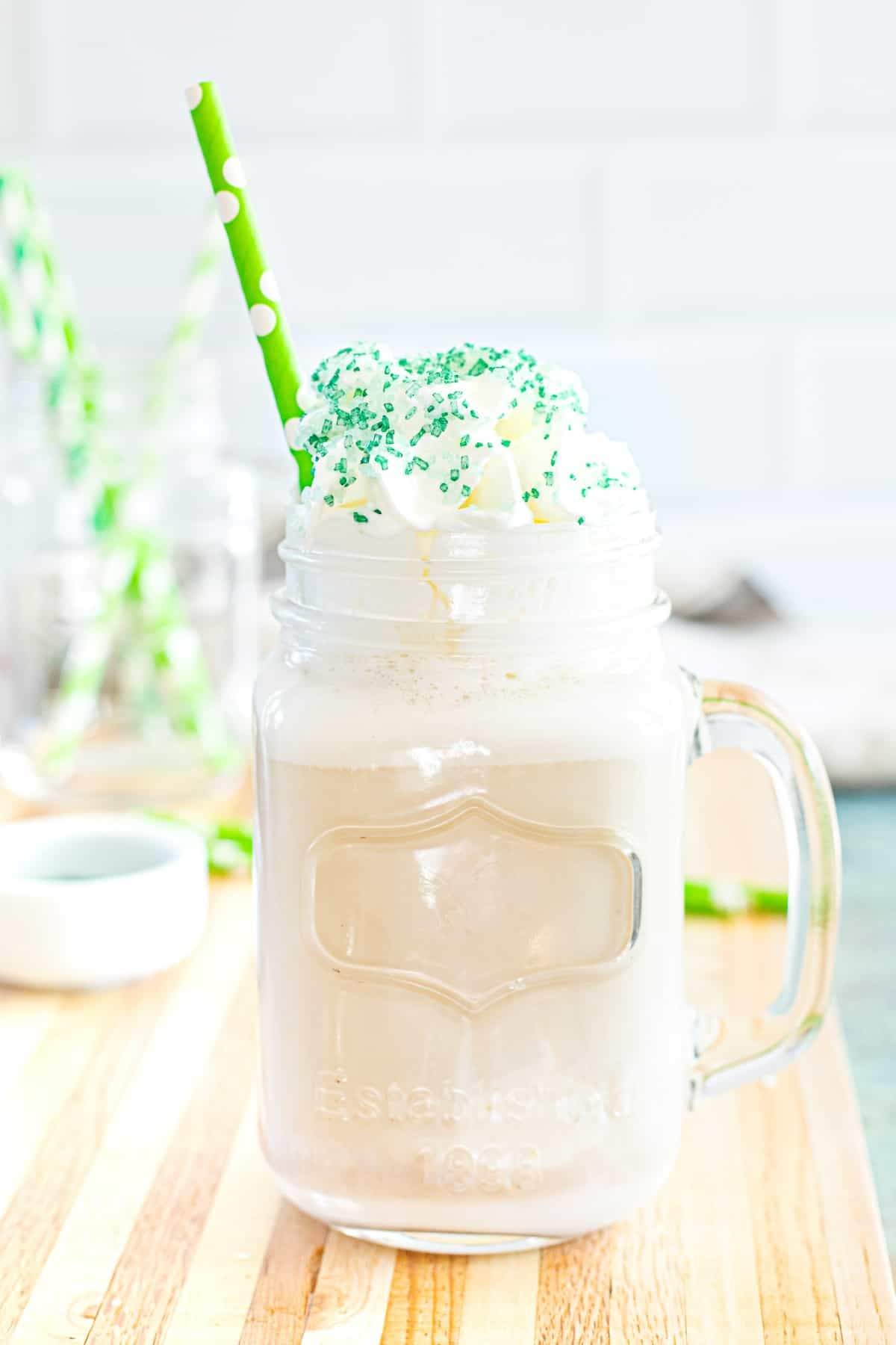 Iced coffee in a glass mug with a green straw and green sprinkles on whipped cream