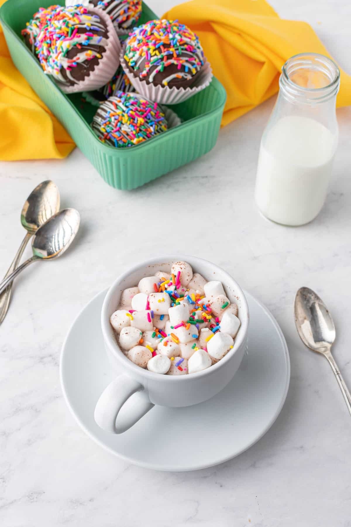 Cup of hot chocolate in a white mug and saucer with lots of mini marshmallows and sprinkles.