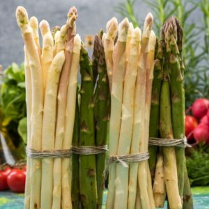 Bunch of asparagus standing on kitchen table.