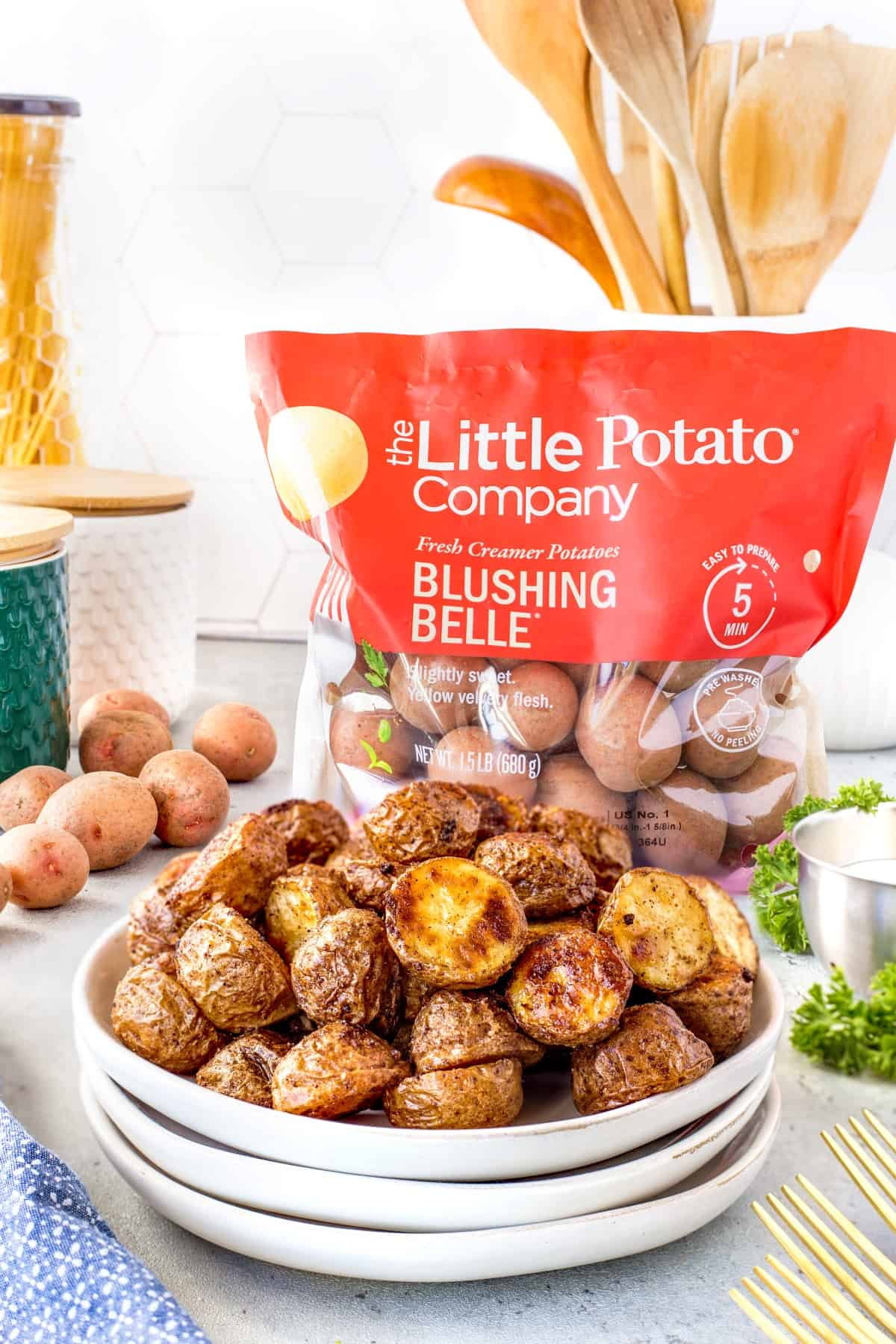 Plate of Cajun Roasted Potatoes with a Little Potato Company bag of potatoes in the background