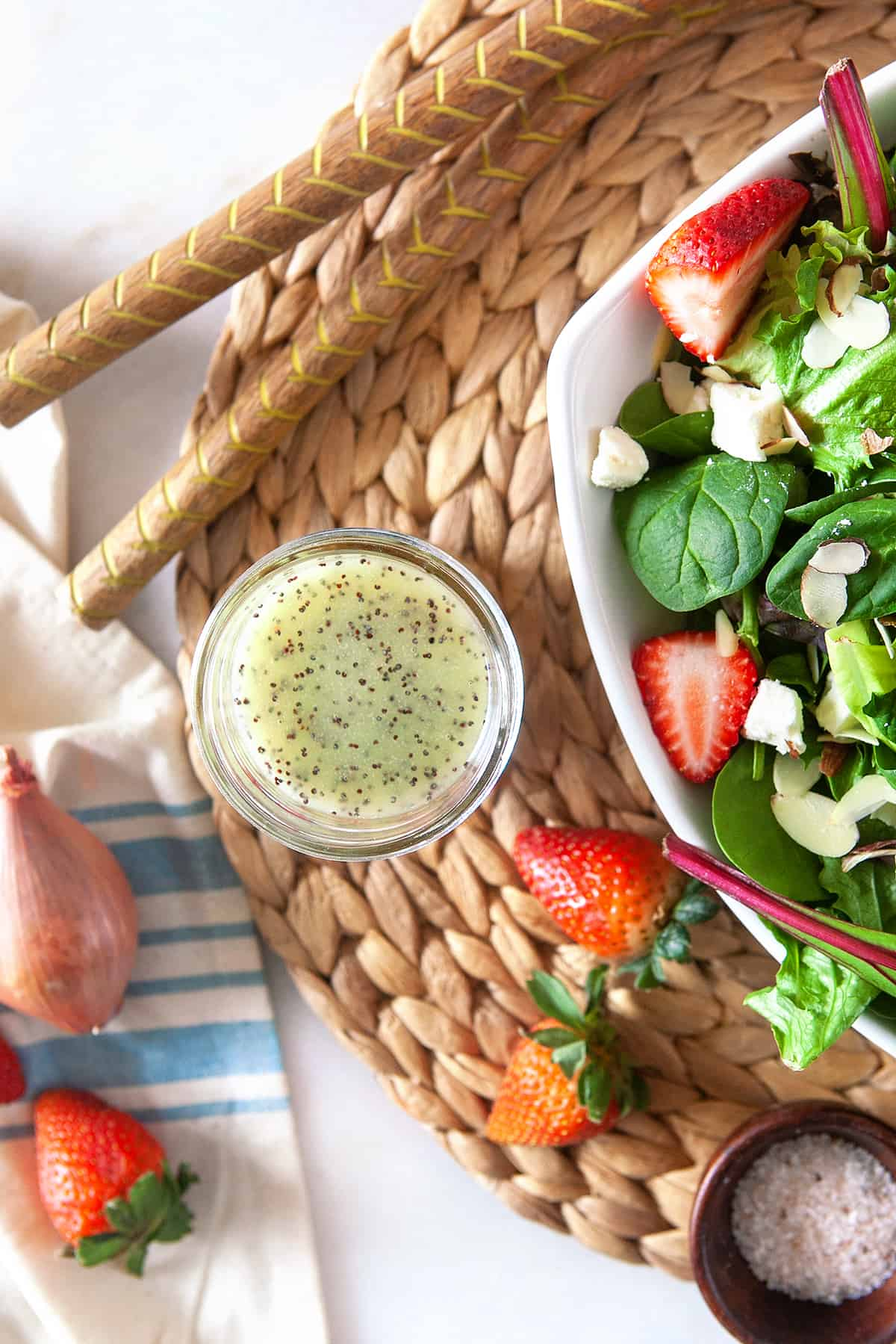 Overhead of homemade poppy seed dressing in a jar on a woven mat with a strawberry salad.