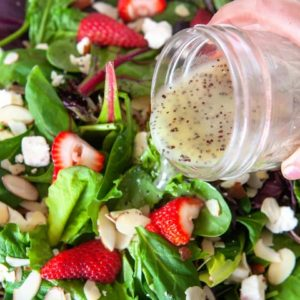 Poppy Seed Dressing being poured from a mason jar over a mixed green salad