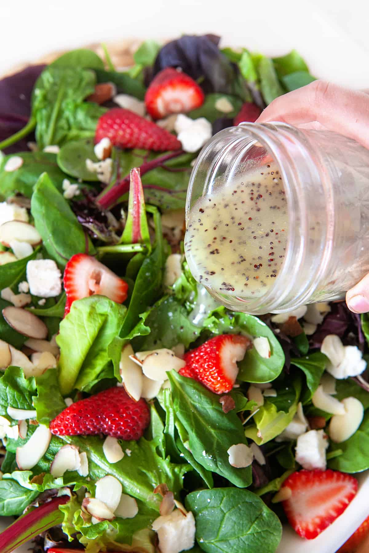 Pouring Poppy Seed Dressing on a salad