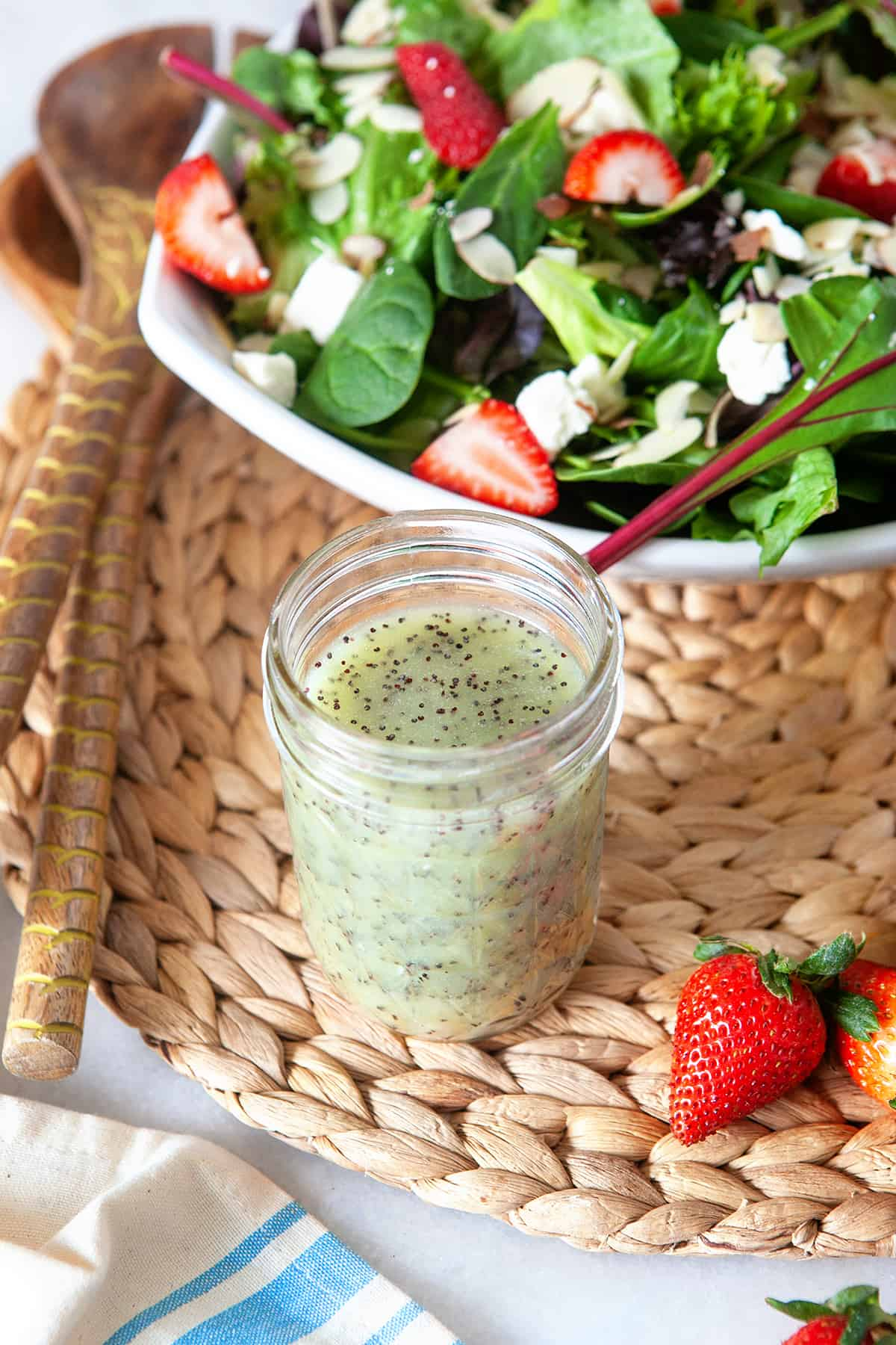 Poppy Seed Dressing on a woven mat with a strawberry salad