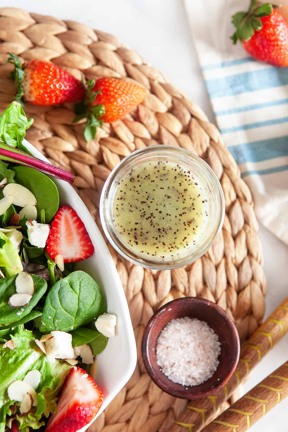 Overhead of poppy seed dressing with a bowl of salt and a strawberry salad