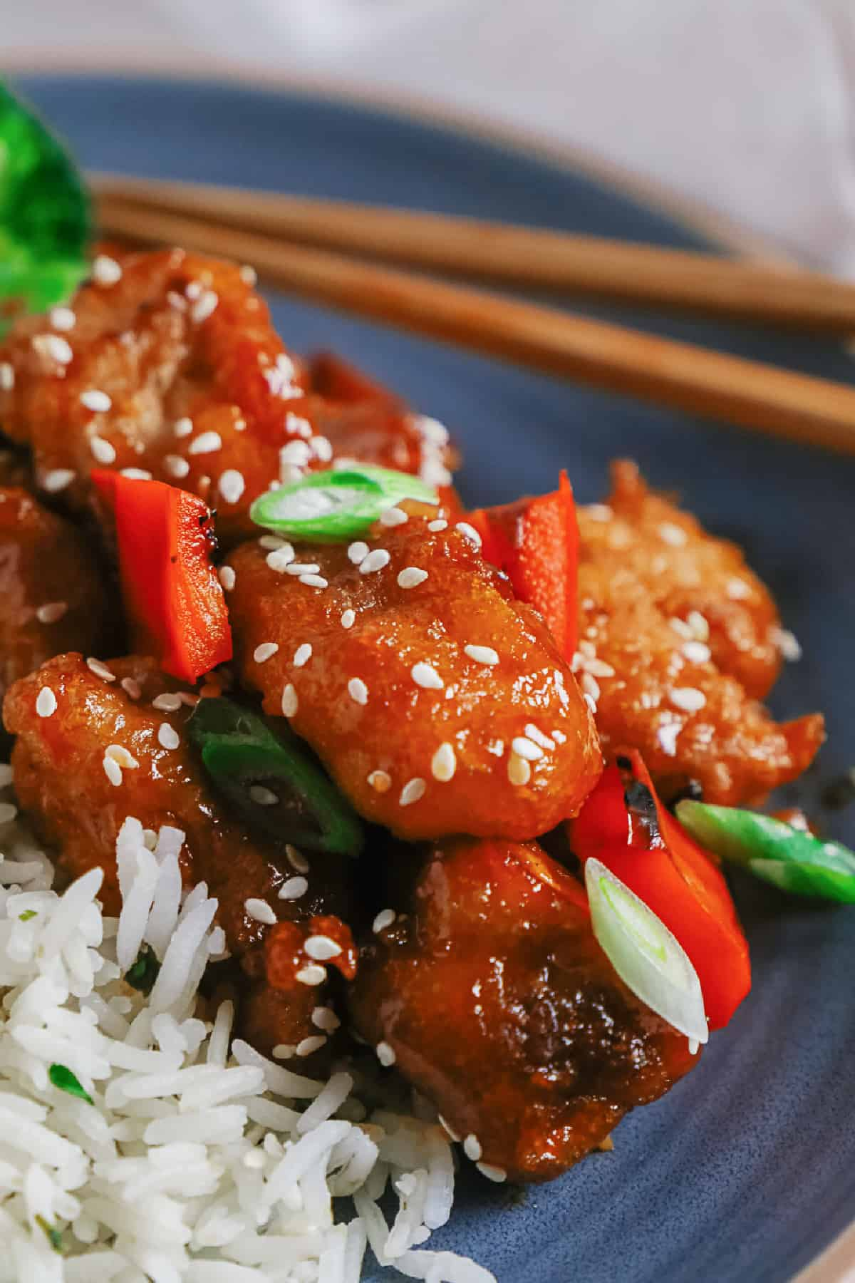 Close up of sweet and sour pork on a plate with rice and chopsticks.