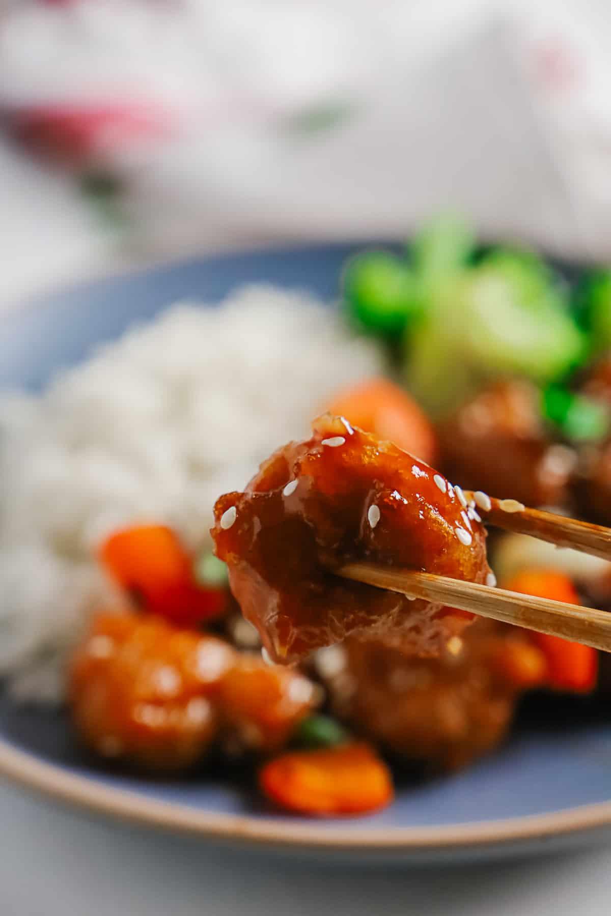 Close up of a piece of crispy pork held by chopsticks.