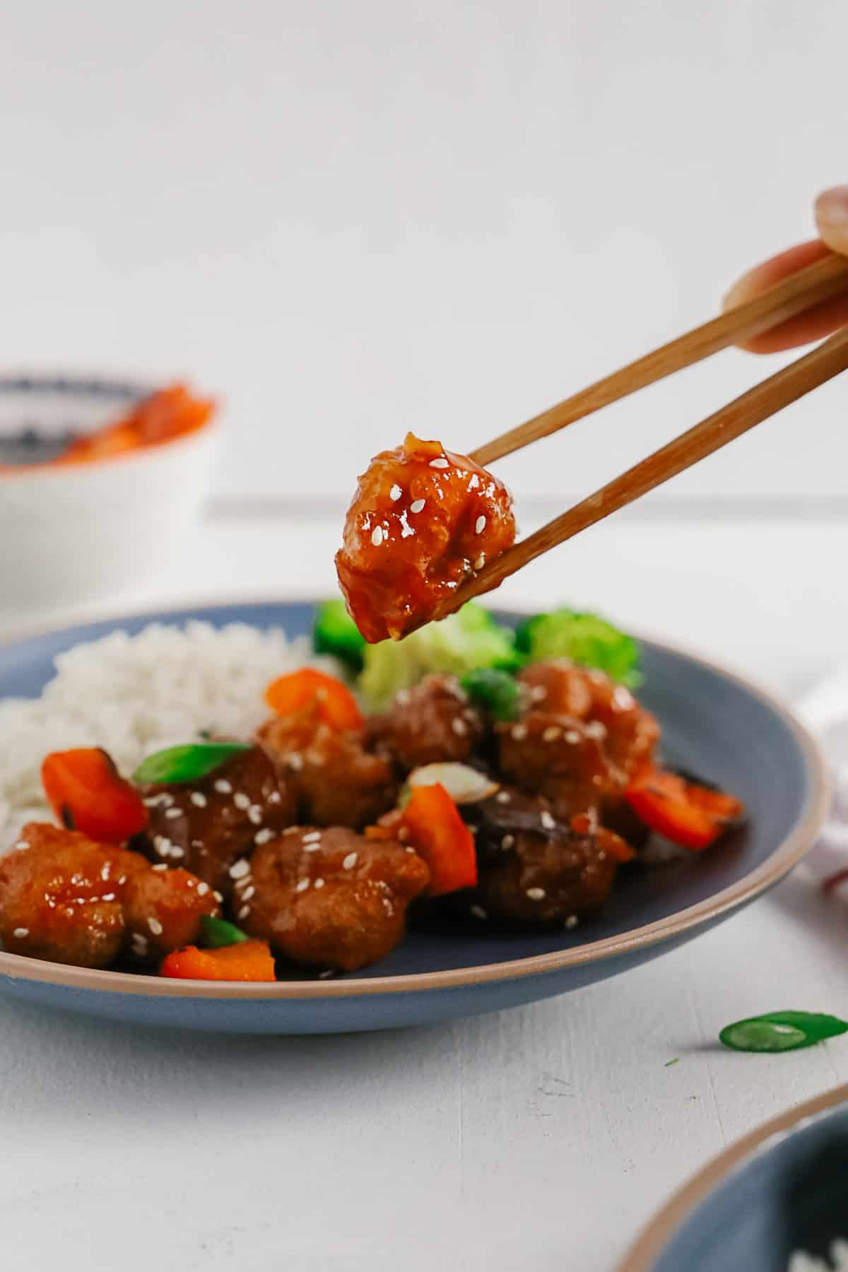 Picking up sweet and sour pork with chopsticks.