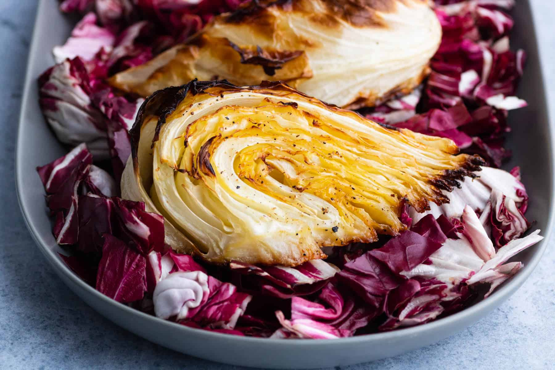 A platter holds a wedge of roasted cabbage on a bed of purple radicchio.