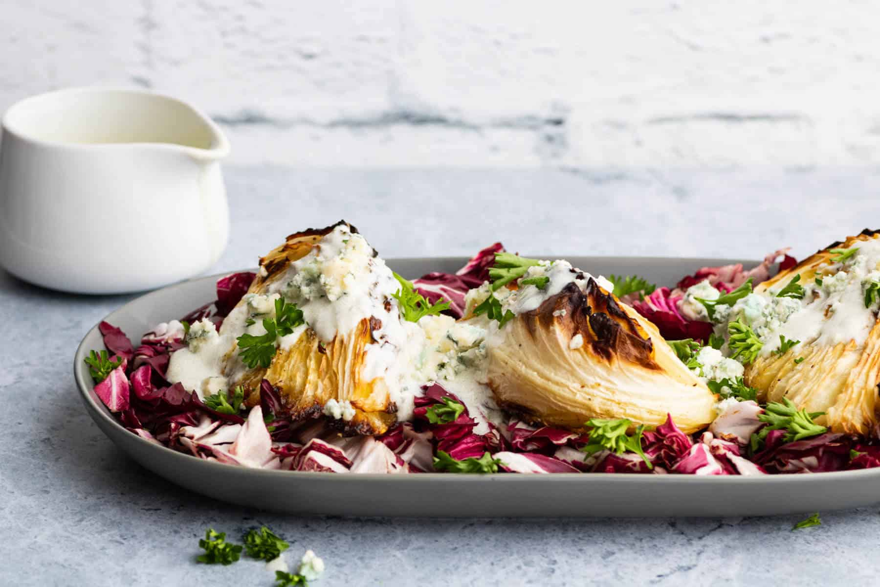 A platter holds roasted cabbage wedges topped with chunky blue cheese sauce all sitting on a bed of purple radicchio.