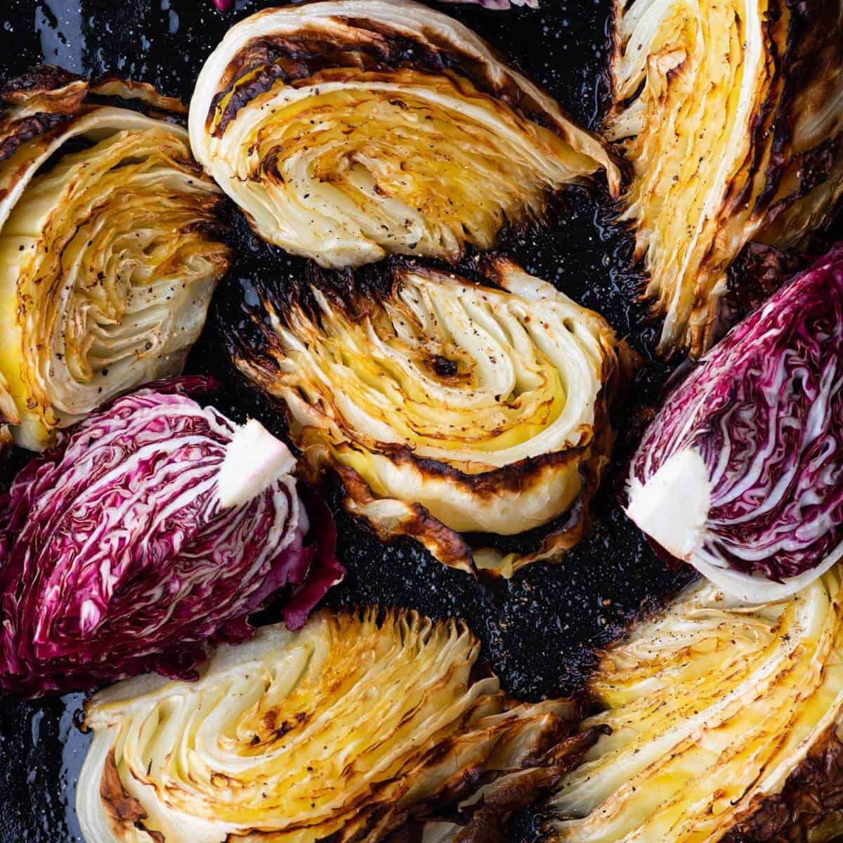 A roasting pan filled with roasted cabbage wedges and purple radicchio.