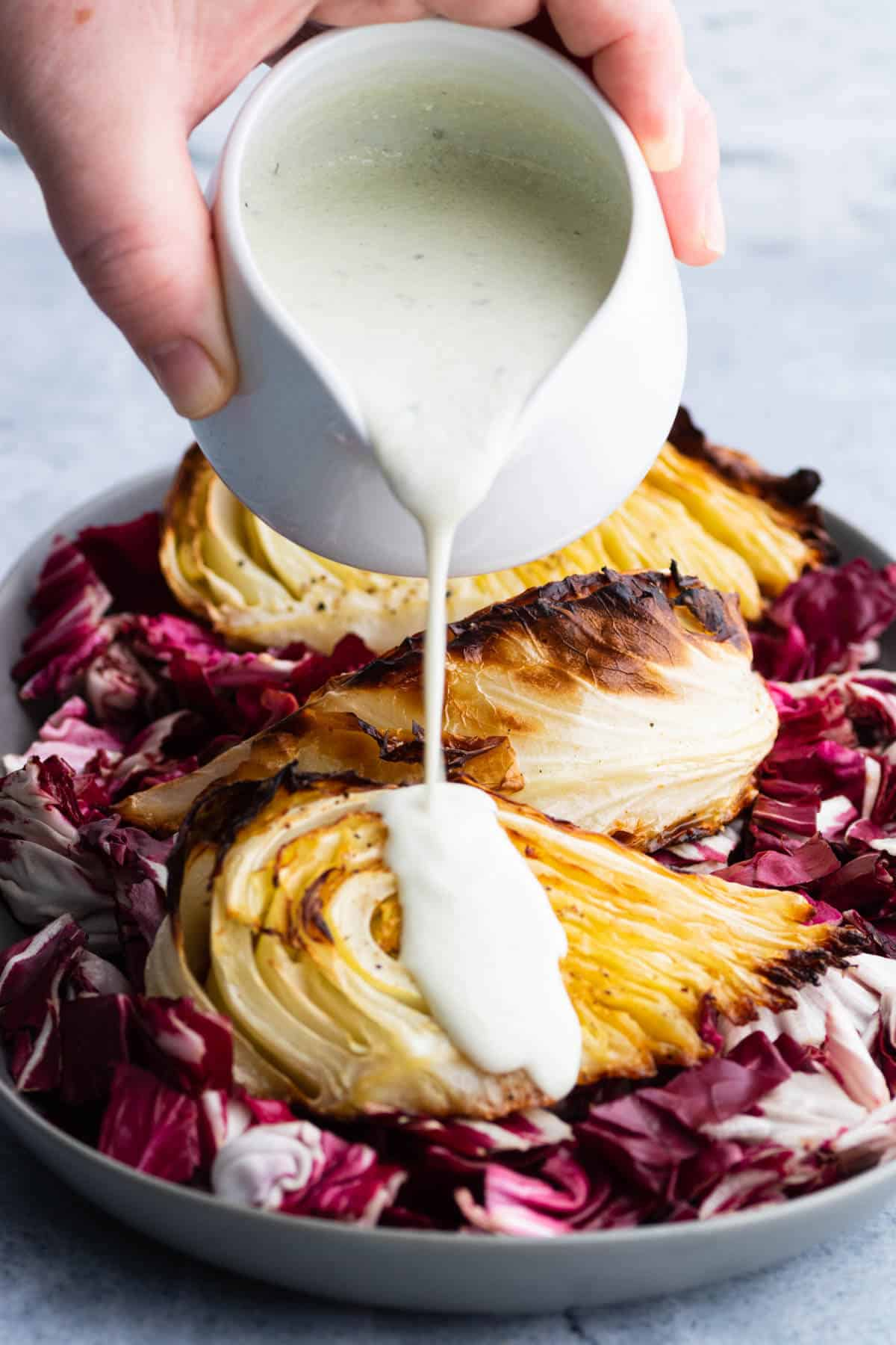 A creamy sauce being poured over roasted cabbage wedges.