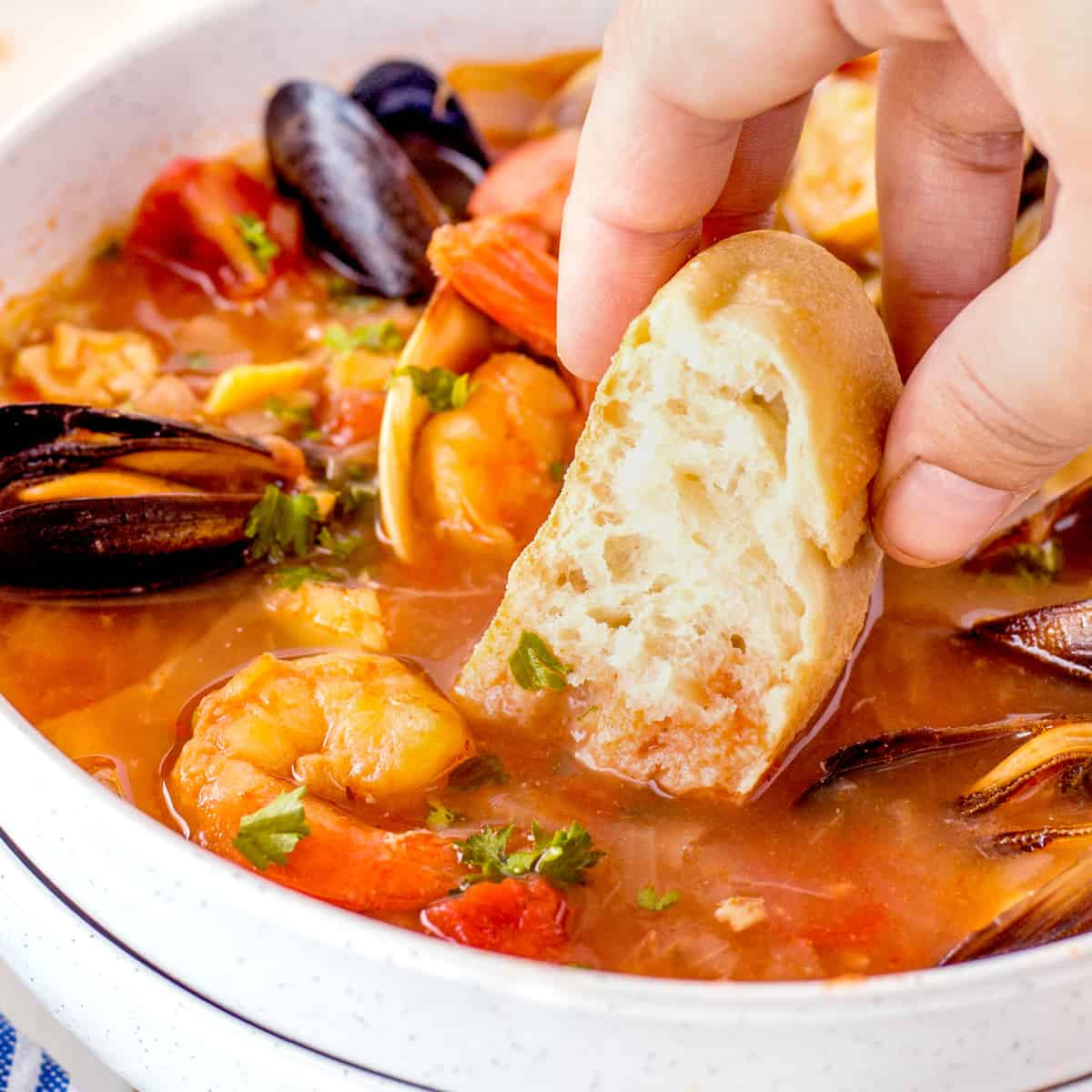 Dipping bread in a bowl of Cioppino, square picture.