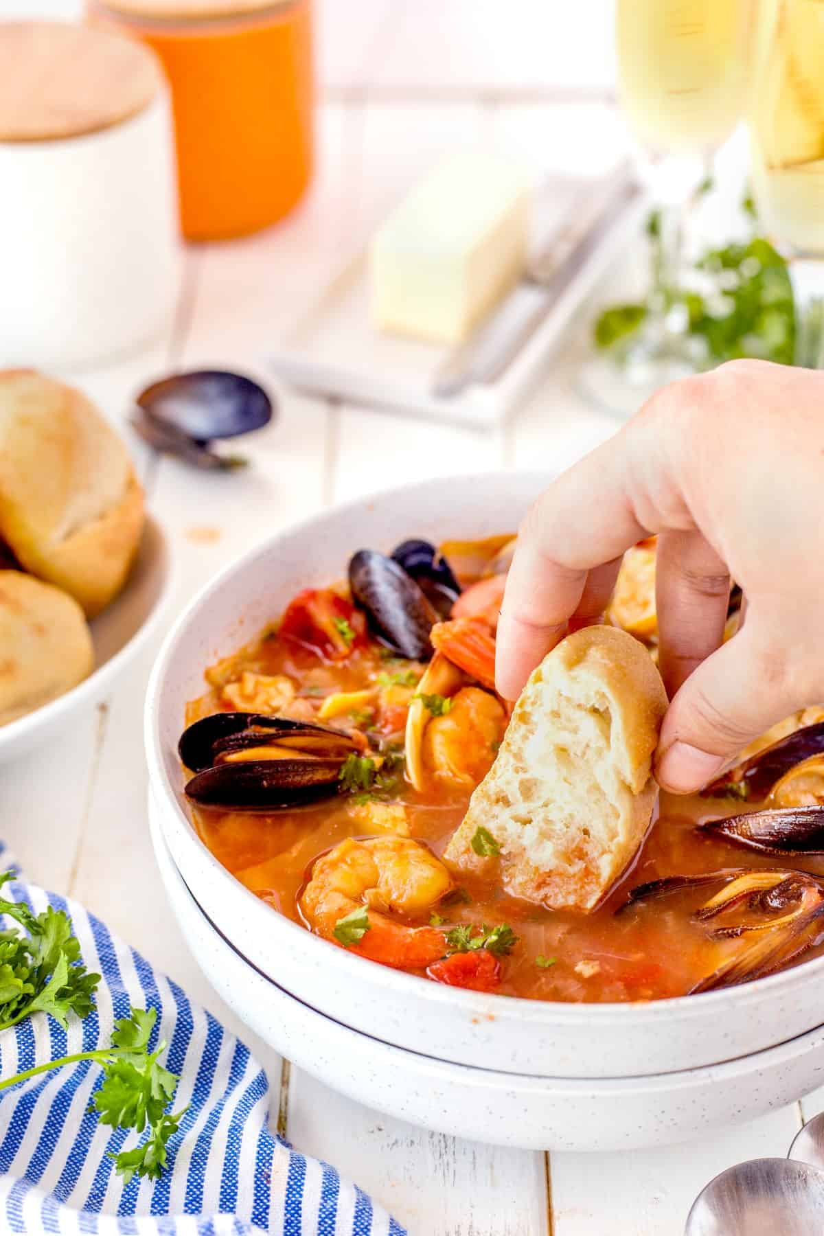 Dipping bread into seafood stew.