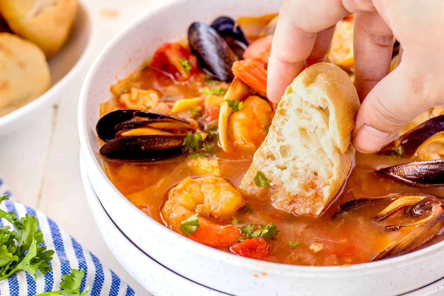 Dipping bread in a bowl of Cioppino, horizontal picture.