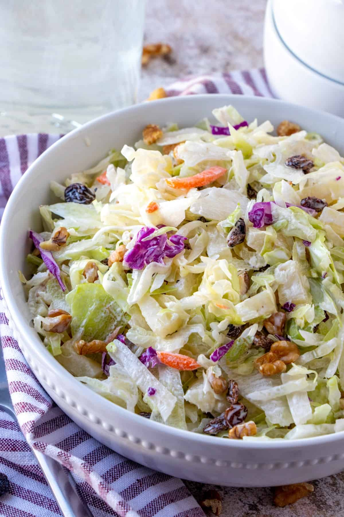 Vertical shot of Pineapple Walnut Raisin Coleslaw in a white ceramic bowl.