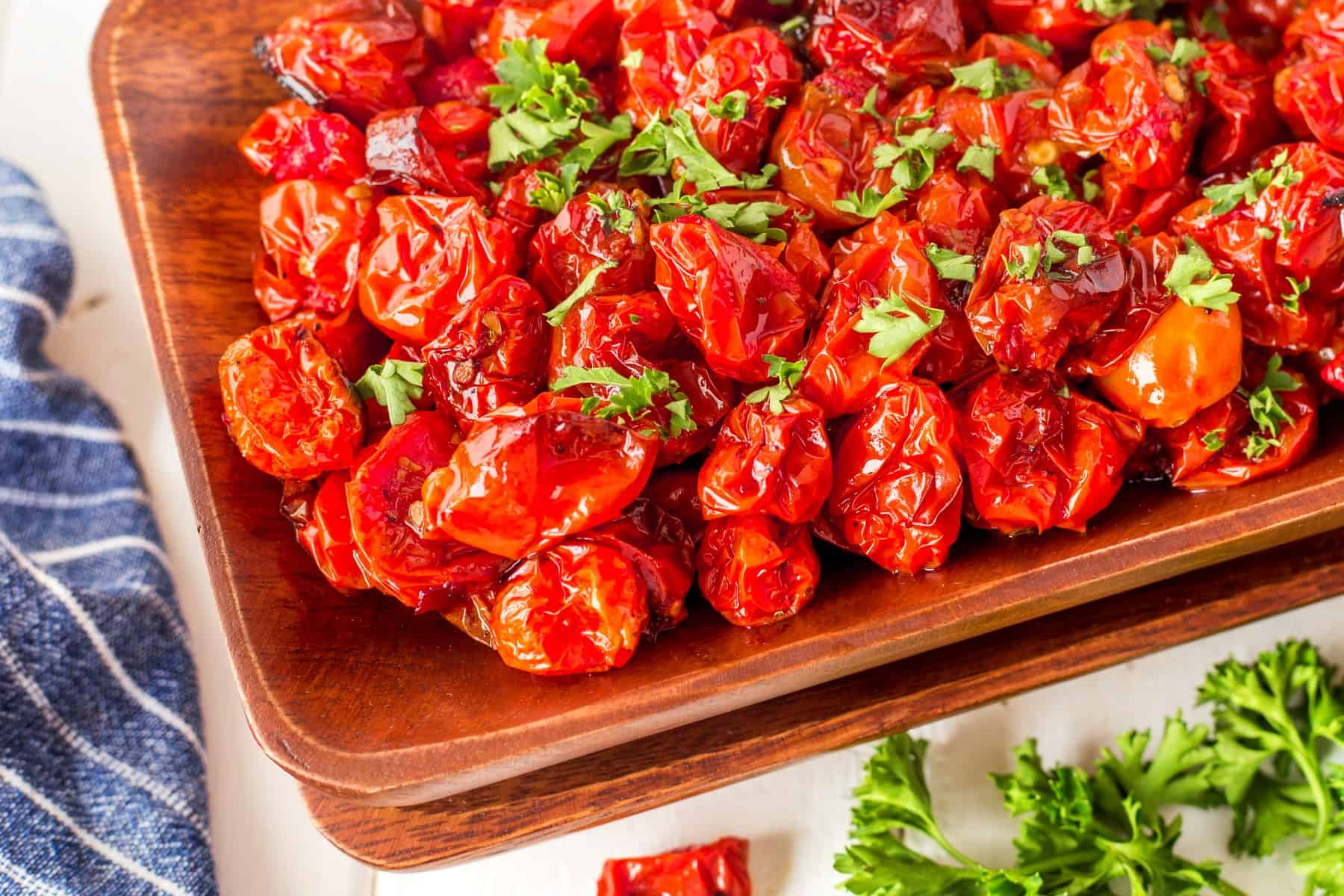 Horizontal of cooked tomatoes in a wooden bowl.