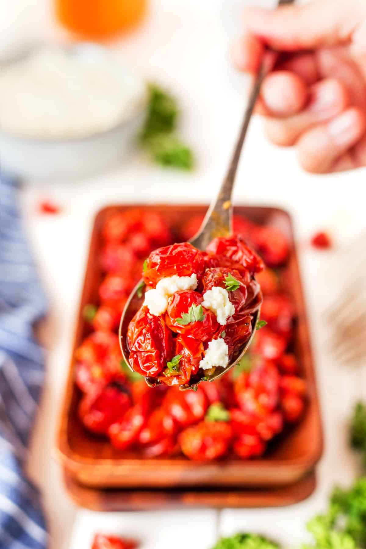 Roasted grape tomatoes and whipped feta on a spoon.
