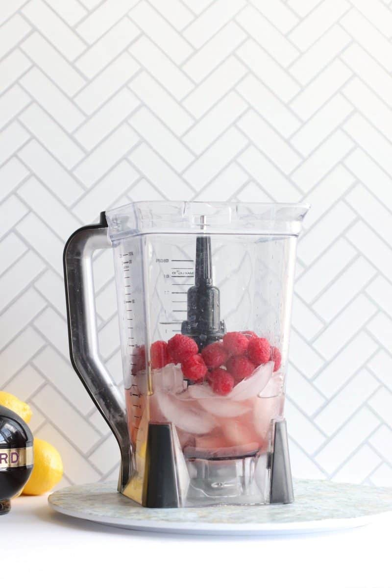 A blender with ice, liquor and raspberries