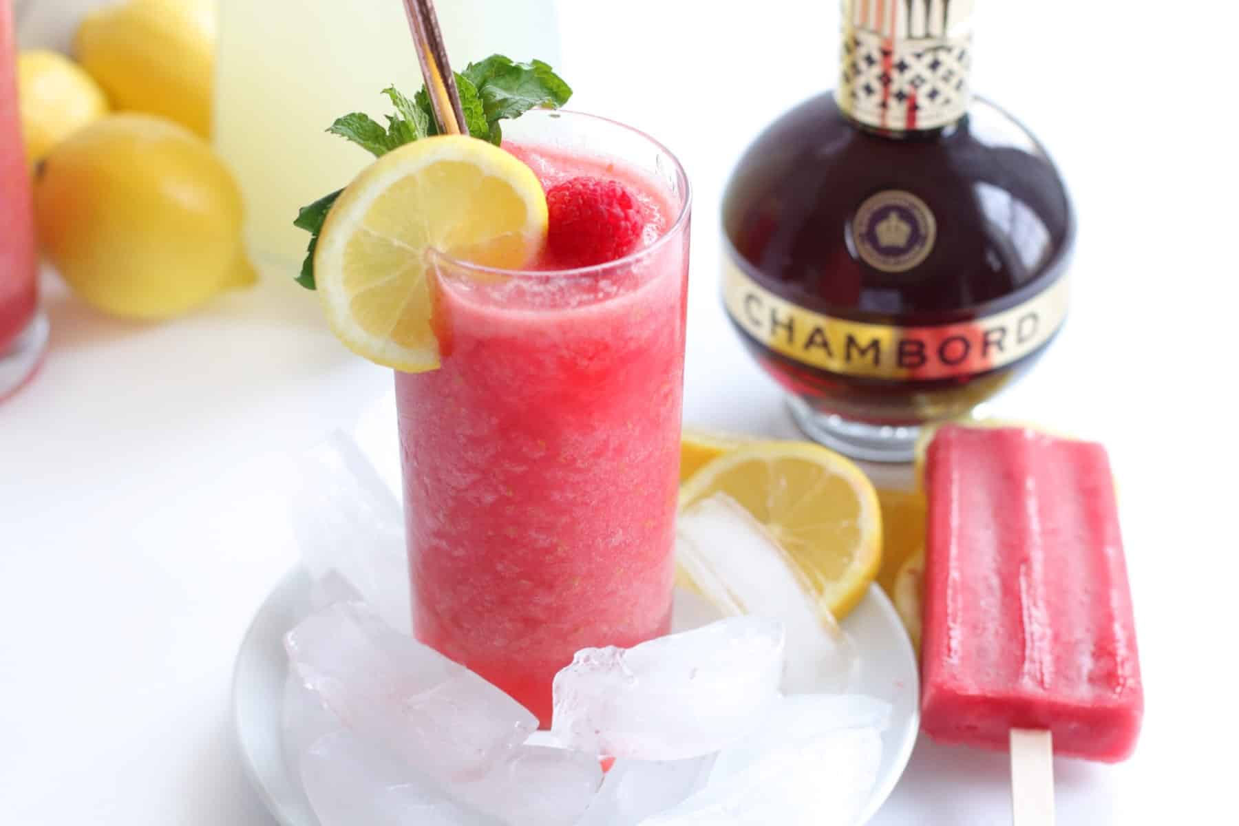 Showing a frozen lemonade in a tall glass with a bottle of Chambord and a raspberry popsicle