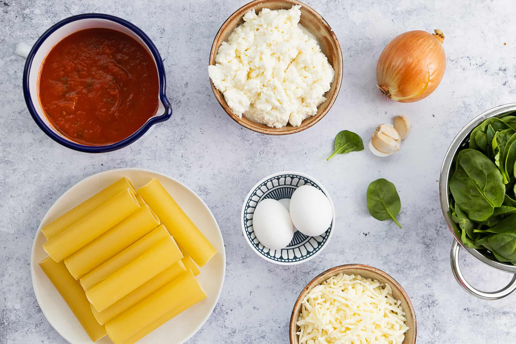 Top view of ingredients for cheese manicotti: pasta shells, tomato sauce, cheeses, eggs, onion, garlic and spinach.