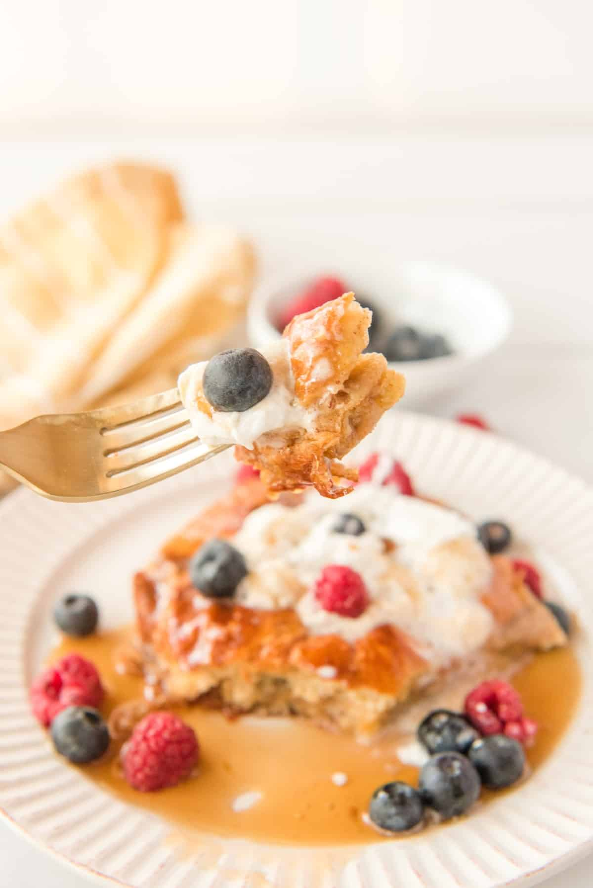 Forkful of French toast and a blueberry.