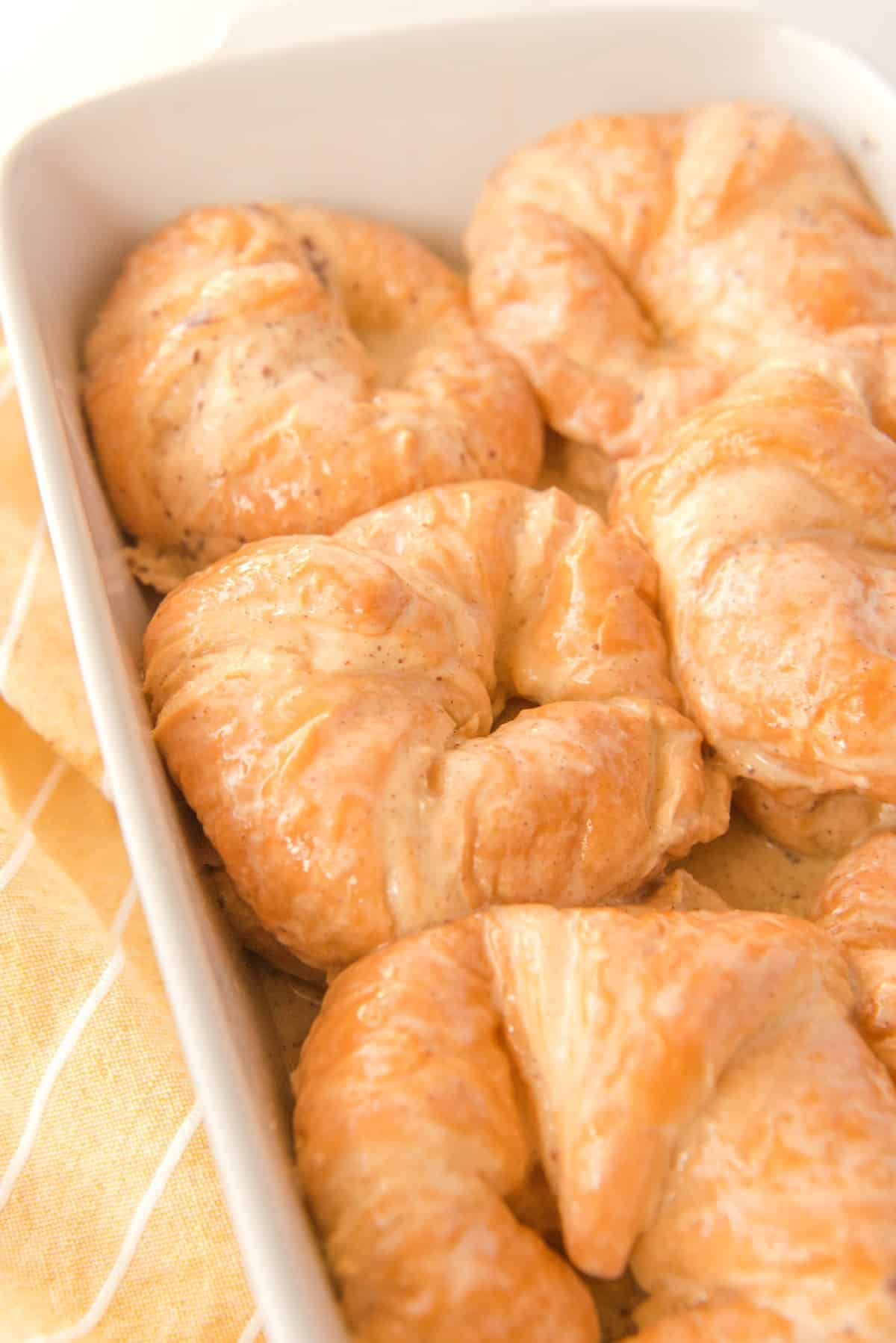 Croissants in a baking dish, soaked in custard