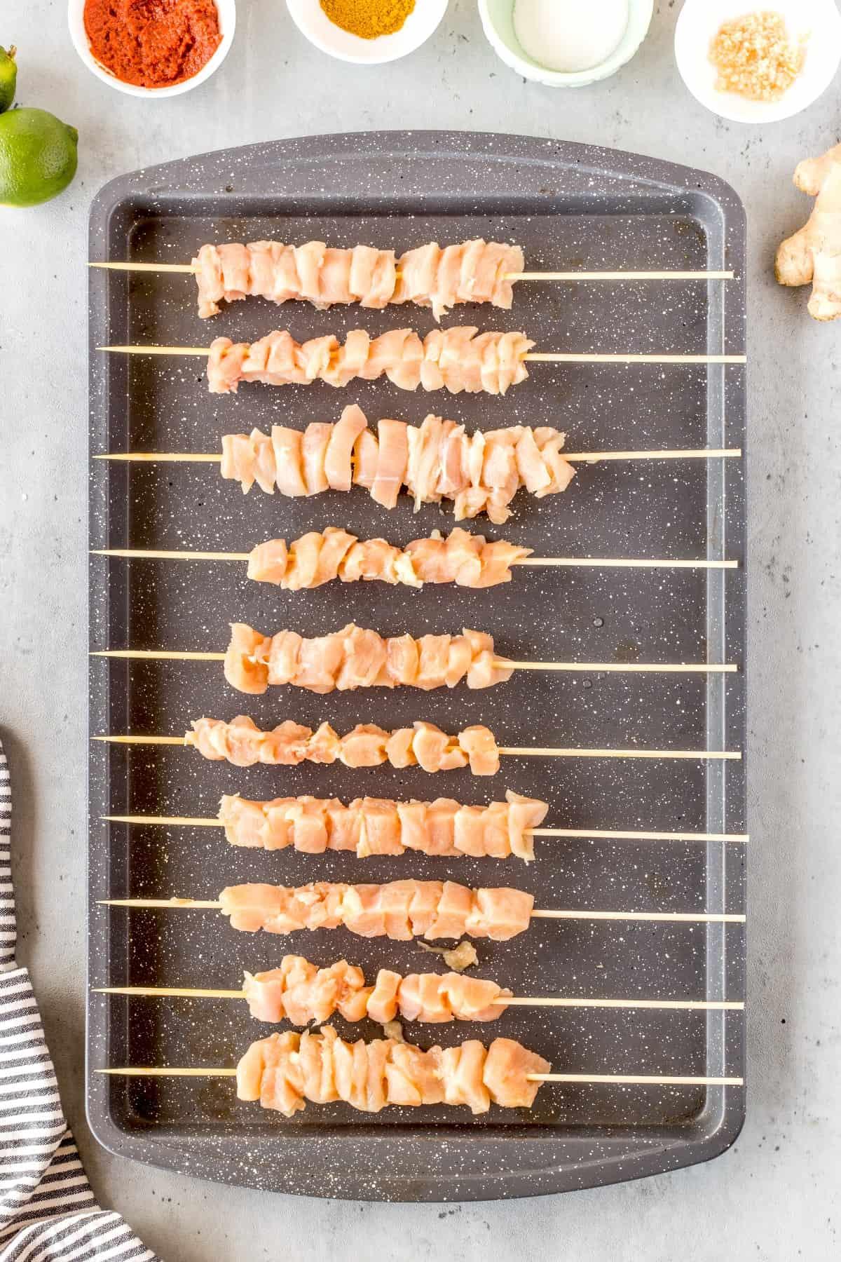 Chicken on skewers on a baking sheet