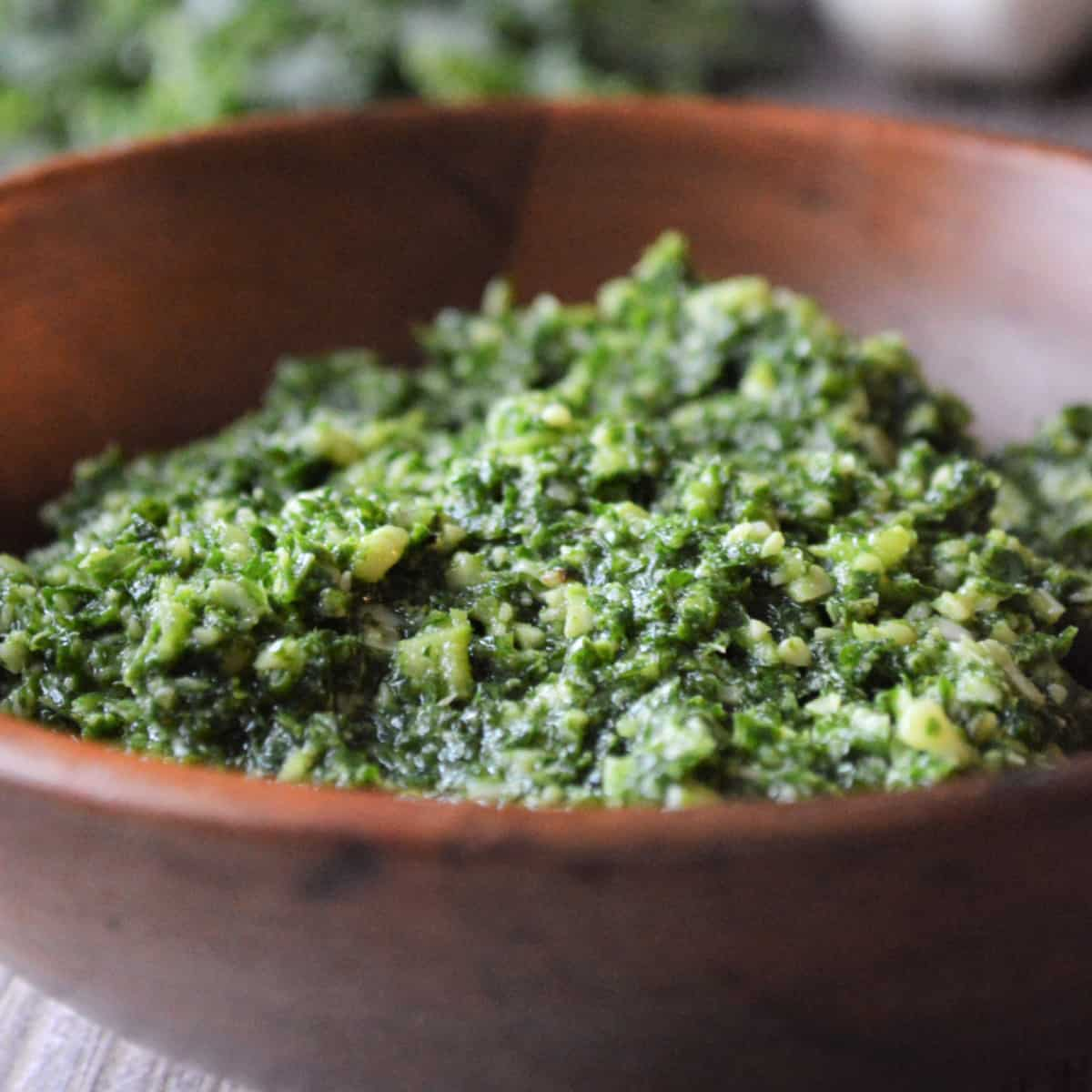 Square photo of a wooden bowl with kale pesto