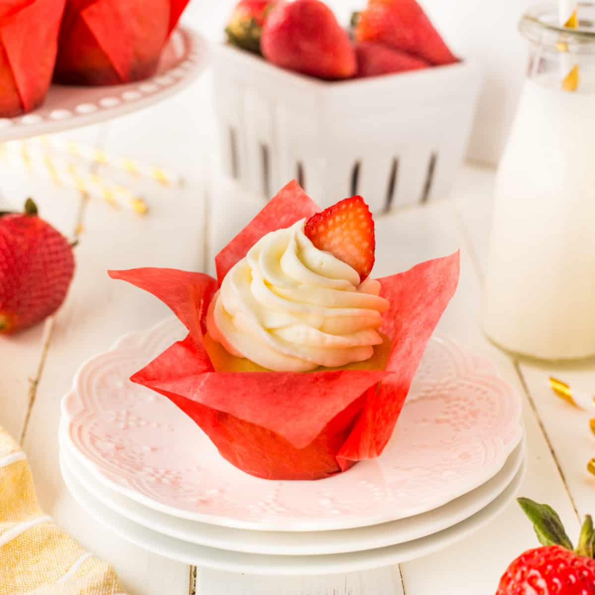 A gorgeous Strawberry Shortcake Cupcake in a red tulip liner on a white plate.