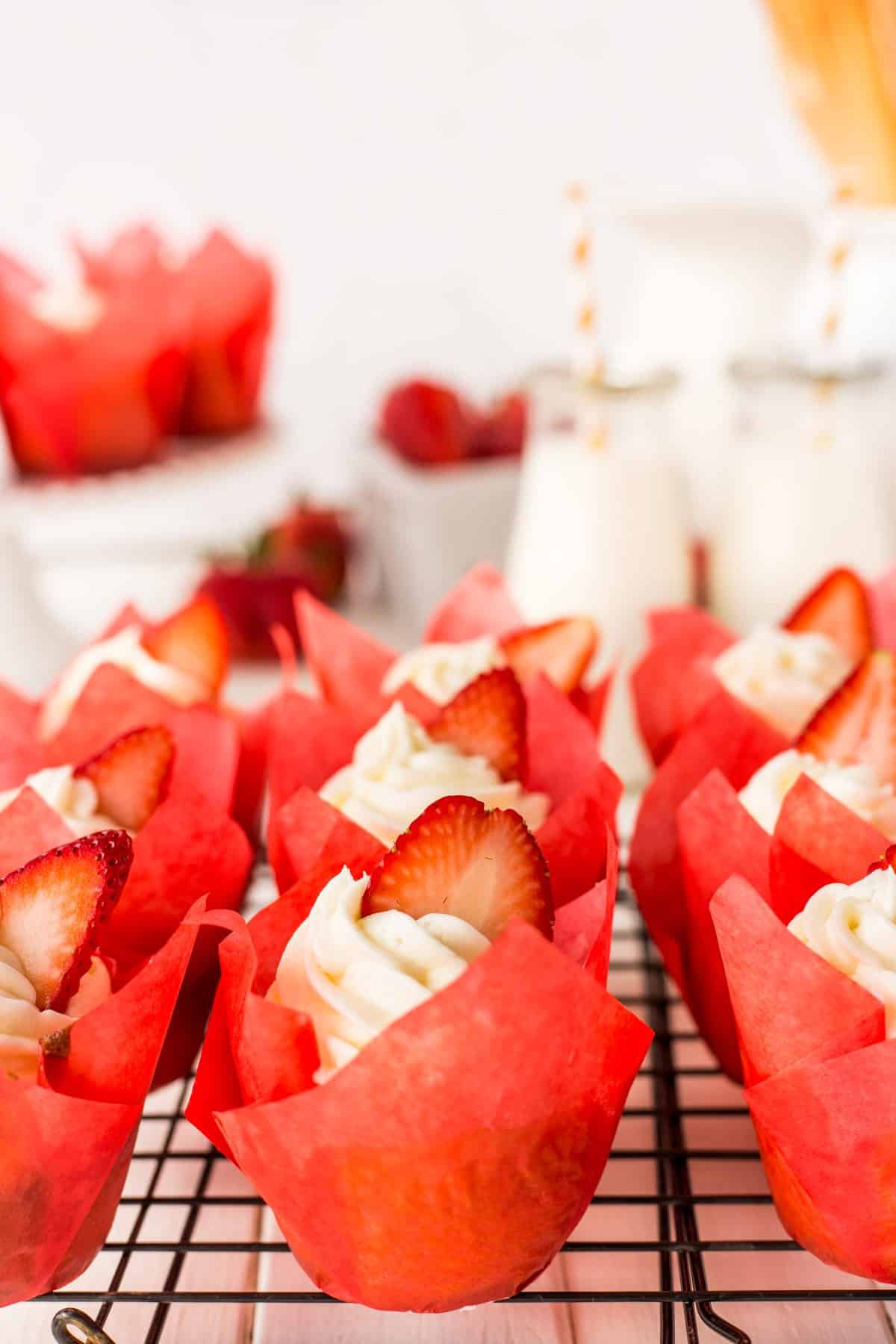 Strawberry Shortcake Cupcakes on a wire rack.
