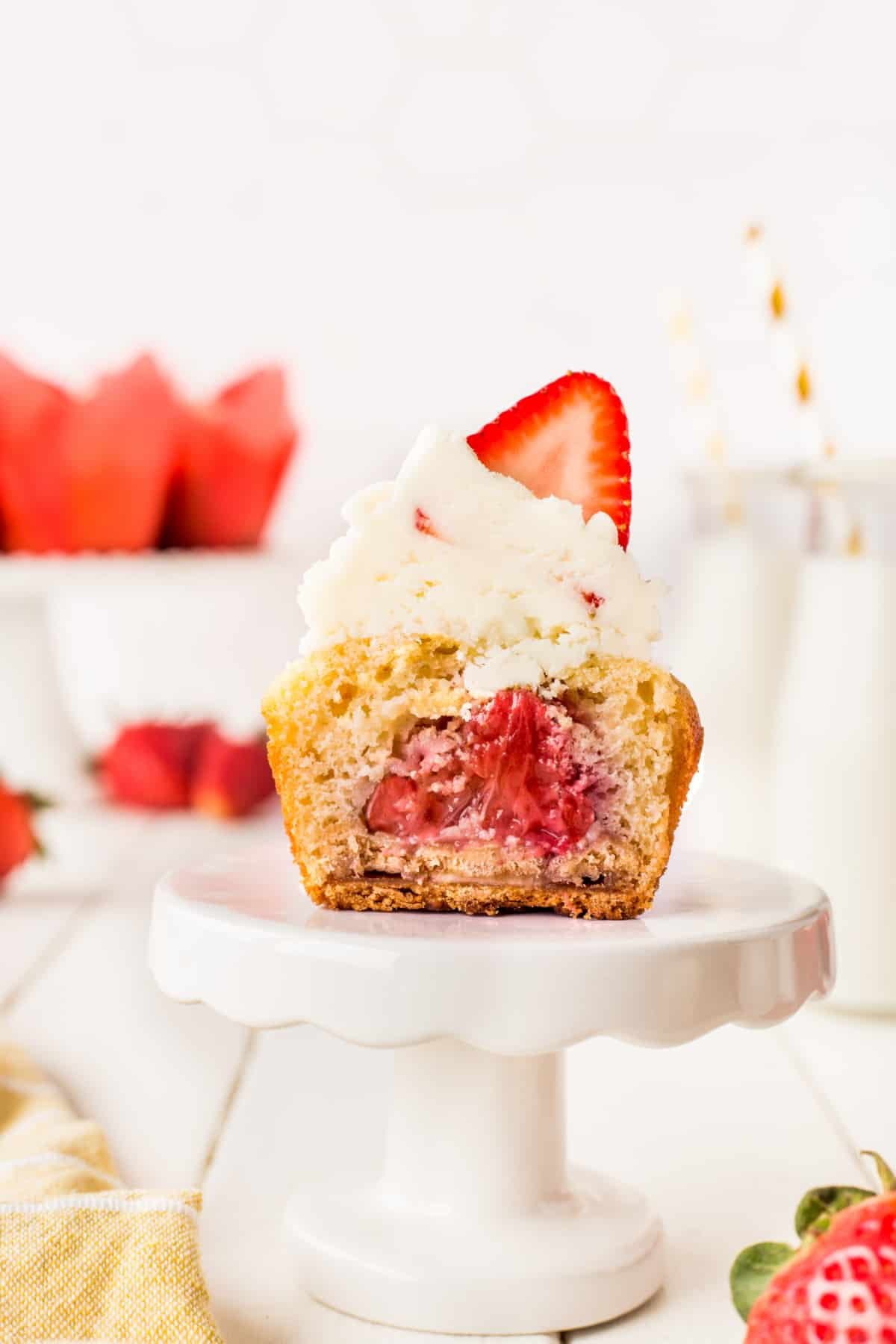 A cupcake sliced in half showing a cooked strawberry inside.