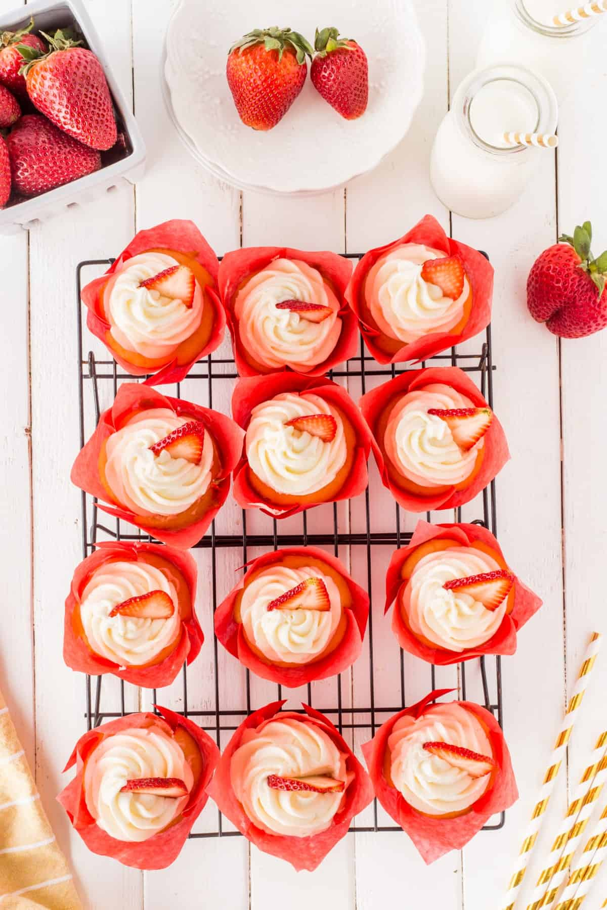 Overhead shot of strawberry cupcakes on a wire rack.