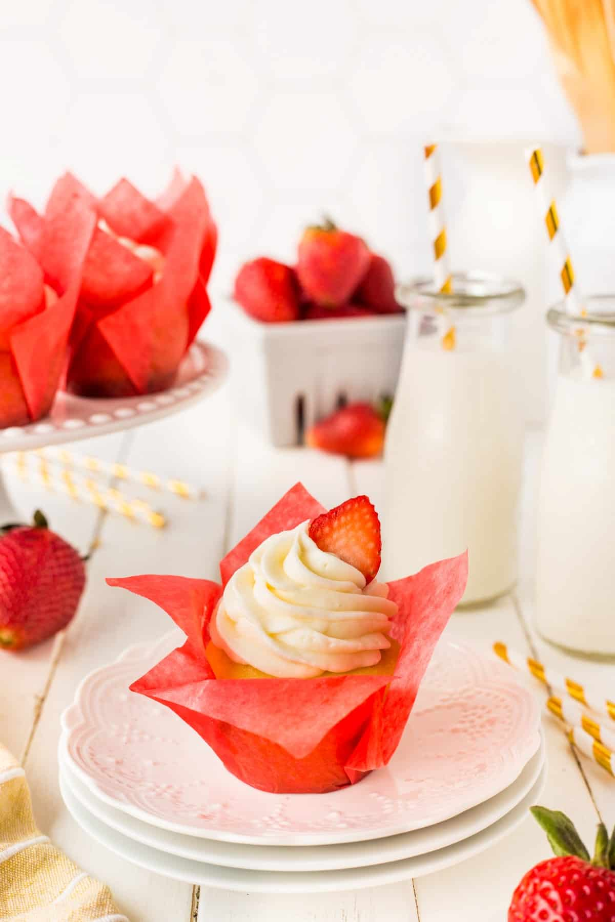 A cupcake on a plate with milk bottles in the background, strawberries and more cupcakes.