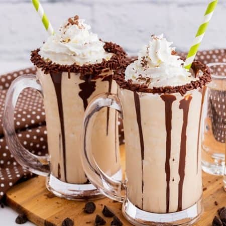 Two chocolate rimmed glass mugs containing frozen mudslide, whipped cream, and chocolate sauce.