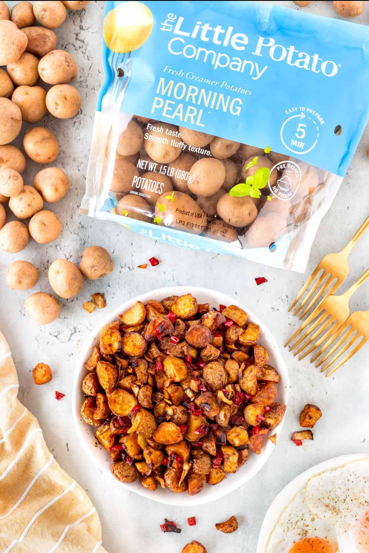 Overhead shot of Air Fryer Home Fries on a plate with packaging from Little Potato Company