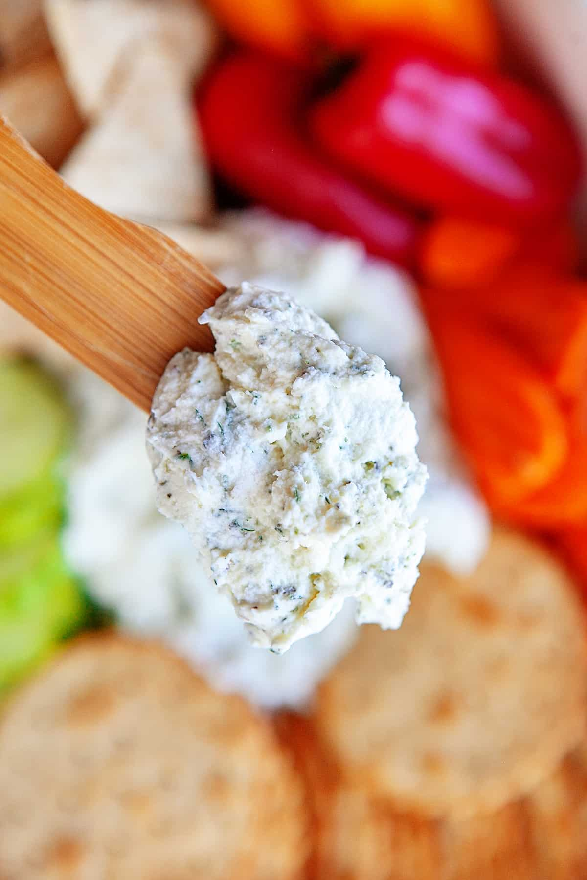 Close up of boursin cheese on a wooden spoon.